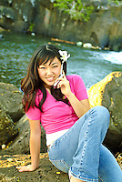 Attractive local teenage girl talking on her cell phone by a lagoon, white orchids in her hair.