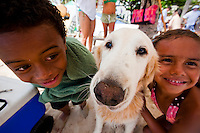 Kids on Waikiki Beach posing with a Golden Retriever dog