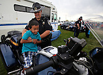Nevada Highway Patrol Lt. Kevin Larsen helps Diego Oseguera, 7, check out a patrol motorcycle during the 11th annual National Night Out hosted by the Carson City Sheriff's Office in Carson City, Nev., on Tuesday, Aug. 6, 2013. <br />