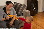 18 month old toddler boy playing with mother holding up toy tiger to her tiger