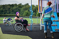 """A mother who is sitting in her wheelchair breastfeeds her baby, just a few weeks old, whist talking to another mother in a playground.<br /> <br /> Image from the breastfeeding collection of the """"We Do It In Public"""" documentary photography picture library project: <br />  www.breastfeedinginpublic.co.uk<br /> <br /> <br /> Berkshire, England, UK<br /> 27/09/2013<br /> <br /> © Paul Carter / wdiip.co.uk"""