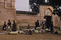 "Un marché au bord du fleuve Niger. Hommes et femmes en larges robes - Ségou, Mali - novembre-décembre 1993<br /> <br /> 1993 - A market on the bank of the Niger River. Men and women in wide robes, mats, bundles of merchandise, concrete elements for ""Le Bamanan Bar Restaurant Dancing Ségou"" with a ""Transport Simaca"" sign."