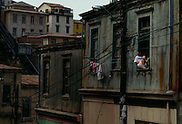 Man sits in window in Valparaiso, Chile, which resembles a medieval European harbor more than a 20th century commercial port.  Narrow streets wind throughout the hills with footpaths.  Ascensores (funicular railways) also transport people up and down the hills. Valpo's opulent mansions and colonial buildings now run down were once a sign of the wealth.