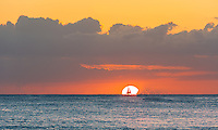 The sun sets on the famous Waikiki Beach of Oahu, Hawaii as a sail boat sails by.