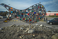 Switzerland. Canton Bern. Rubigen. A metal fish sculpture on the center of a traffic roundabout. Fish are gill-bearing aquatic craniate animals that lack limbs with digits. The art piece was created by Rubigen primary school students  (2014 - 2015) under the supervision of Margherita Furter and Stefan Käsermann. Cars on the road and pedestrians walking on sidewalk. Parking place in front of Denner supermarket. Denner is a discount supermarket chain in Switzerland. It is Switzerland's third largest supermarket chain after Migros and Coop with 11.4% market share. It is owned by the Federation of Migros Cooperatives since 2007. A roundabout is a type of circular intersection or junction in which road traffic is permitted to flow in one direction around a central island, and priority is typically given to traffic already in the junction. Rubigen is a municipality in the Bern-Mittelland administrative district in the canton of Bern. 14.12.2020 © 2020 Didier Ruef