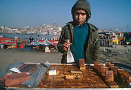 Child employed to sell traditional pastry in the street in Istanbul, Turkey - Child labor as seen around the world between 1979 and 1980 - Photographer Jean Pierre Laffont, touched by the suffering of child workers, chronicled their plight in 12 countries over the course of one year.  Laffont was awarded The World Press Award and Madeline Ross Award among many others for his work.