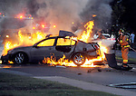 Manchester Fire, Rescue and EMS work to knock down the flames to get to the driver, after the car hit a pole and burst into flames, Thursday, June 19, 2014,  on East Center Street in Manchester.  The driver died in the fire, a burning passenger who  ran from the car died later from his injuries. (Jim Michaud / Journal Inquirer)