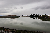Overcast skies, marking the changing seasons, are reflected in the still waters of the small boat lagoon at San Leandro's Marina Park on San Francisco Bay.