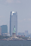 The Statue of Liberty, New York Harbor, with the Goldman Sachs Tower in the background.