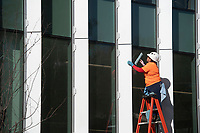 A worker cleans windows Monday Nov. 16, 2020 at the Fayetteville Public Library's new addition. The expansion of 82,500-square-feet will nearly double the size of the 88,000-square-foot main library. Visit nwaonline.com/201117Daily/ and nwadg.com/photos. (NWA Democrat-Gazette/J.T.WAMPLER)