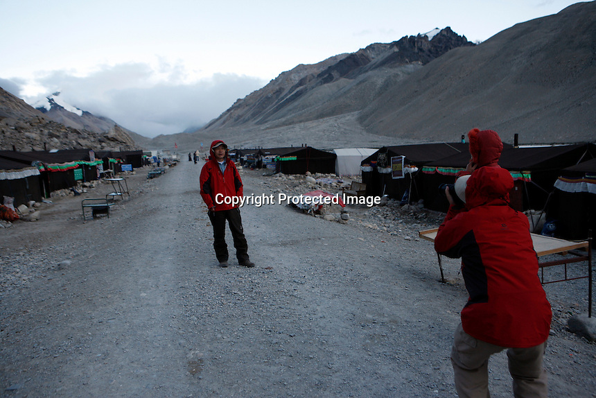"""China started building a controversial 67-mile """"paved highway fenced with undulating guardrails"""" to Mount Qomolangma, known in the west as Mount Everest, to help facilitate next year's Olympic Games torch relay./// Chinese tourists take photographs at the tent village near Everest base camp.<br /> Tibet, China<br /> July, 2007"""