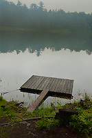 Wooden raft on foggy lake