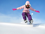 Young girl running down snow bank.