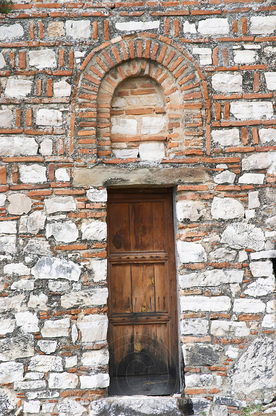The Hagia Triada Church. Detail of an old wooden door and arched window. Berat upper citadel old walled city. Albania, Balkan, Europe.