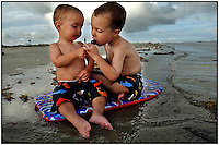 Two young boys, brothers, play with one another during a family vacation to the beach near Charleston, SC. There are three photos in this series of the boys with the suckers. Model released image may be used to illustrate other destinations or concepts.