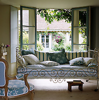 In this country living room, a wrought-iron daybed has been matched with a striped mattress and contrasting striped cushions