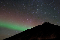 Aurora borealis, (northern lights) and starry sky over the Brooks Range, Arctic, Alaska.