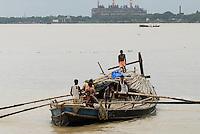 INDIA Westbengal Calcutta Kolkata, wooden freight boat on river hooghli, backside coal power station  / INDIEN Westbengalen, Kalkutta, Holzboot mit Fraucht auf dem Fluss Hugli, ein Nebenfluss des Ganges, Hintergrund Kohlekraftwerk