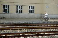 Man walking a bicycle along the platform of a train station between Beijing and Datong, China.