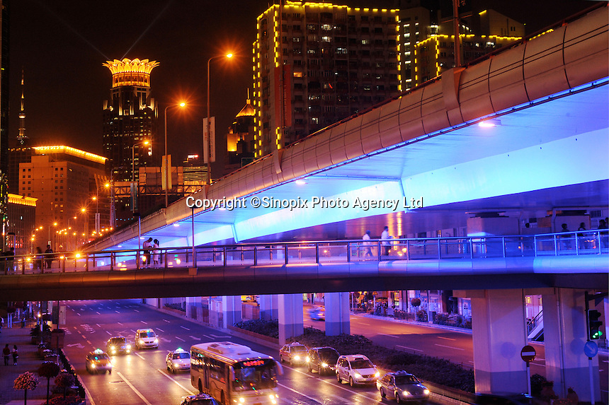 A highway overpass is lit up at night, below the highway, there are pedestrians cross a footbridge. Since the population and the automobiles are increasing in Shanghai, more driveways, pavements and highways are needed, Shanghai, China..17 May 2010