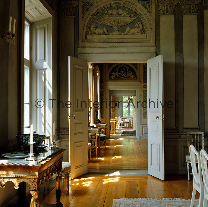 A view from the dining room through the enfilade of rooms on the first floor - the hand-painted overdoor strikes a gastronomic note