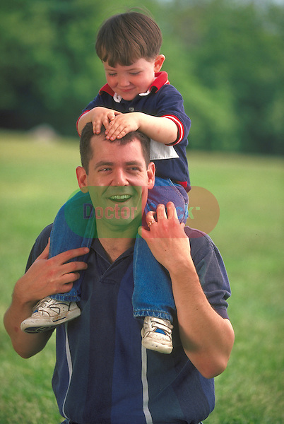 laughing father carrying young boy on shoulders