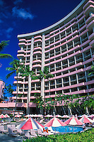 Tourists sunbathe under umbrellas on Waikiki Beach near the famous Royal Hawaiian Hotel.