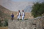 13 June 2013, Onaba Village, Onaba District, Panjshir Province,  Afghanistan.  Local village men Mohammad Panjshiri (left), Ahmad Zia (centre) and Najibullah Alimi walk along the wall of the irrigation canal they have built alongside the Panjshir River at their village of Onaba in Onaba District. The water is used to feed their crops which is wheat at the moment.  Canals are being built and rehabilitated under the Irrigation Restoration and Development Project (IRDP). While some donors are supporting reconstruction/development of specific rivers the Emergency Irrigation Rehabilitation Project (EIRP) is instrumental in the Govt of Afghanistan's launch of a national irrigation scheme. Typical rehabilitation works would include improving canal intake structures, conveyance channels and aqua ducts. Picture by Graham Crouch/World Bank