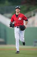 John Ziznewski (5) of the Kannapolis Intimidators jogs off the field with his hands full of protective equipment after having coached first base during the game against the Delmarva Shorebirds at CMC-Northeast Stadium on June 6, 2015 in Kannapolis, North Carolina.  The Shorebirds defeated the Intimidators 7-2.  (Brian Westerholt/Four Seam Images)