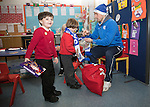 St Johnstone players took some festive cheer to Fairview School in Perth gving out selection boxes and gifts to the pupils…David Wotherspoon wraps a Saints scarf around primary school pupil Jack watched by fellow pupil Logan<br />