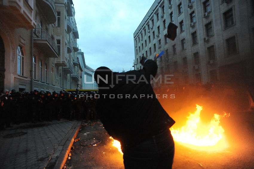 A protester trhows  objects againsts a riot policemen deployment (Bekrut) during the storm of the Kiev city council building, after  the Ukrainian  government's decision to stall on a deal that would bring closer ties with the European Union.