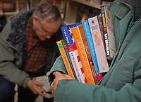 A woman holds her book choices as anther customer sorts though the last books to be sold at the Westerville, Ohio, B. Dalton bookstore on the final day of sales at the suburban store. The store, one of the smallest in the B. Dalton chain, was closing after nearly two decades tucked in the corner of a building housing an insurance company and a balloon store.