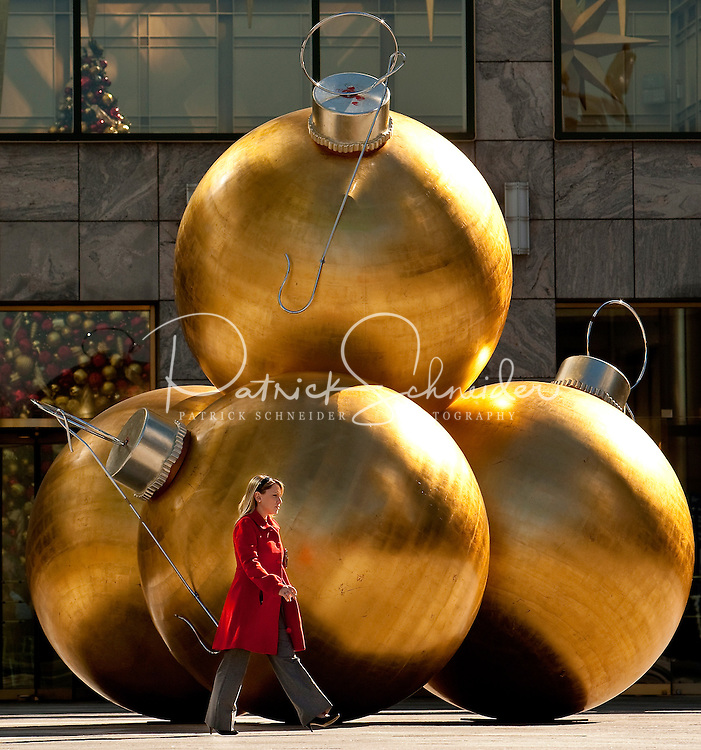 A business women dressed in a red coat walks past large gold Christmas ornaments outside of the Wachovia corporate headquarters in Uptown Charlotte.