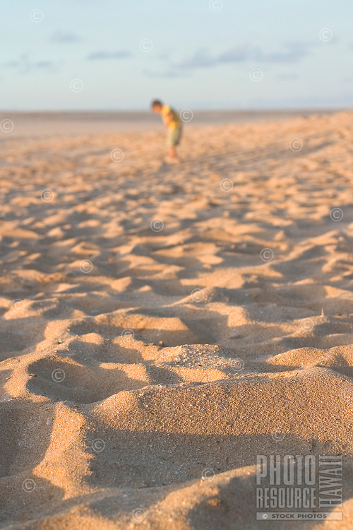 Small boy playing on sandy beach. Focus on foreground.