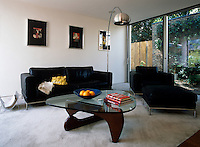 A modern black leather sofa, matching armchair and footstool and a glass-topped coffee table in the living area