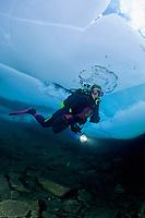scuba diver diving under the ice in a frozen mountain lake, Sassolo lake, Sambuco valley, Ticino, Switzerland
