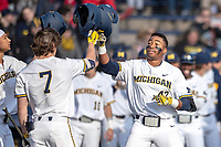 Michigan Wolverines outfielder Jordan Nwogu (42) is greeted at the plate by teammate Jesse Franklin (7) after his lead off home run against the Rutgers Scarlet Knights on April 26, 2019 in the NCAA baseball game at Ray Fisher Stadium in Ann Arbor, Michigan. Michigan defeated Rutgers 8-3. (Andrew Woolley/Four Seam Images)
