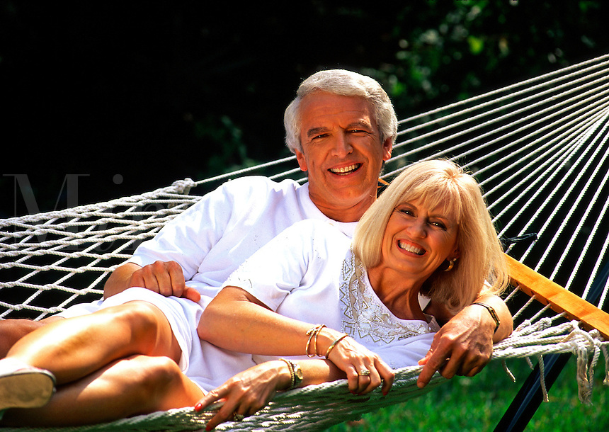 A smiling mature couple relaxes on a hammock.