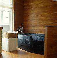 Stunning in its simplicity the slate bath and tongue and groove surround of the bathroom in a house in Normandy