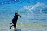 Man launching his fishing net into the crystal water, Siviri Beach, Efate Island, Vanuatu.