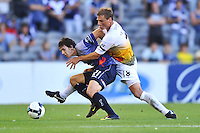 MELBOURNE, AUSTRALIA - JANUARY 26, 2010: Robbie Kruse from Melbourne Victory holds back Ben Sigmund from Wellington Phoenix in round 19 of the A-league match between Melbourne Victory and Wellington Phoenix FC at Etihad Stadium on January 26, 2010 in Melbourne, Australia. Photo Sydney Low www.syd-low.com