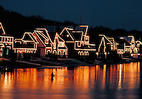 A row of boat houses is outlined with lights. Night shot with a rower in the lake in the foreground. Philadelphia.