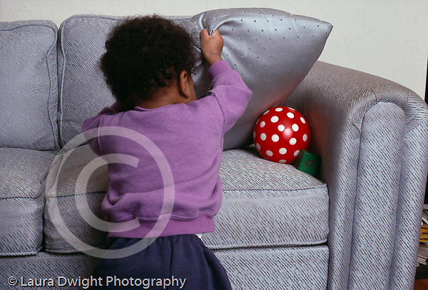 girl  11 mos. old Piaget Object Permanence Test finding toy behind cushion horizontal