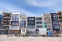Nederland - Amsterdam- 2021.     Op het nieuw aangelegde Centrumeiland worden huizen gebouwd naar eigen ontwerp. Het wordt een van de duurzaamste ontwikkellocaties van de stad, mede door het systeem van warmte koude opslag WKO. Daarmee worden de huizen op het hele eiland voorzien van warmte en koude uit de bodem. Foto ANP / Hollandse Hoogte / Berlinda van Dam