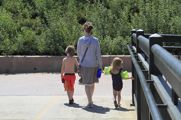 Mother taking her son and daughter to swim at the beach, Denver, Colorado. .  John offers private photo tours in Denver, Boulder and throughout Colorado. Year-round Colorado photo tours.