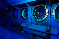 Tourists peer out the portholes of the Atlantis Submarine, eager to see Hawaii's unique sea creatures.