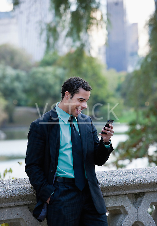 USA, New York, New York City Businessman with cell phone in park