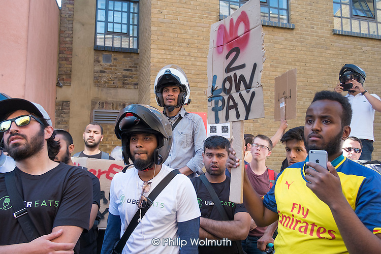 Striking UberEats food delivery couriers protest outside the group's London HQ over pay cuts.
