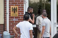 Zentrale Auslaenderbehoerde und BAMF-Aussenstelle in Eisenhuettenstadt.<br /> Bundesinnenminister Thomas de Maiziere und brandeburgs Ministerpraesident Dietmar Woidke besuchten am Donnerstag den 13. August 2015 die Zentrale Auslaenderbehoerde und BAMF-Aussenstelle in Eisenhuettenstadt. Sie liessen sich von Mitarbeitern die Situation in der Einrichtung zeigen und erklaeren, sprachen mit Fluechtlingen und besichtigten das auf dem Gelaende befindliche Abschiebegefaengnis.<br /> Der Besuch des Bundesinnenministers und des Ministerpraesidenten wurde von etwa 40 Journalisten begleitet.<br /> Im Bild: Fluechtlinge vor einem der Verwaltungsgebaeude.<br /> 13.8.2015, Eisenhuettenstadt/Brandenburg<br /> Copyright: Christian-Ditsch.de<br /> [Inhaltsveraendernde Manipulation des Fotos nur nach ausdruecklicher Genehmigung des Fotografen. Vereinbarungen ueber Abtretung von Persoenlichkeitsrechten/Model Release der abgebildeten Person/Personen liegen nicht vor. NO MODEL RELEASE! Nur fuer Redaktionelle Zwecke. Don't publish without copyright Christian-Ditsch.de, Veroeffentlichung nur mit Fotografennennung, sowie gegen Honorar, MwSt. und Beleg. Konto: I N G - D i B a, IBAN DE58500105175400192269, BIC INGDDEFFXXX, Kontakt: post@christian-ditsch.de<br /> Bei der Bearbeitung der Dateiinformationen darf die Urheberkennzeichnung in den EXIF- und  IPTC-Daten nicht entfernt werden, diese sind in digitalen Medien nach §95c UrhG rechtlich geschuetzt. Der Urhebervermerk wird gemaess §13 UrhG verlangt.]