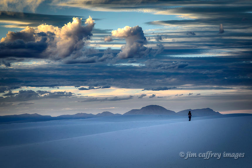 A lone hiker on the dunes at White Sands National Monument at twilight.